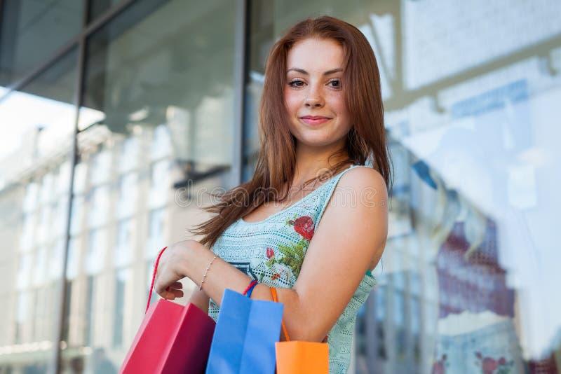 有五颜六色的购物袋的年轻美丽的女孩 销售的季节 免版税库存照片