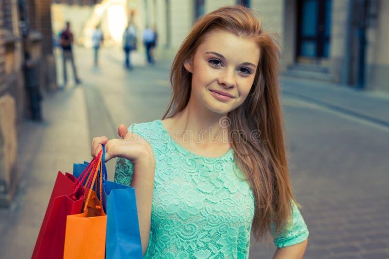 有五颜六色的购物袋的年轻美丽的女孩 销售的季节 免版税图库摄影