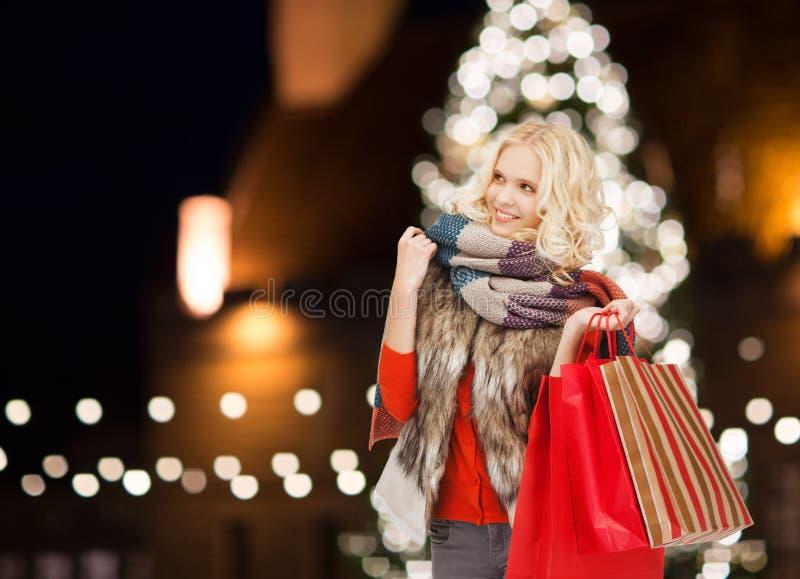 有五颜六色的购物袋的微笑的妇女 免版税库存照片