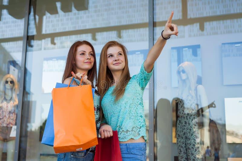 有五颜六色的购物袋的女孩指向某事的 销售额 免版税库存照片