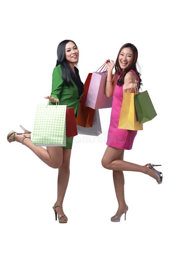 有五颜六色的购物袋的微笑的两个亚洲人妇女 库存图片