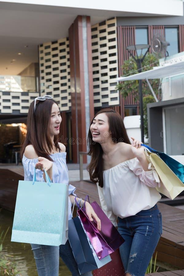 有五颜六色的购物袋的愉快的亚裔妇女在部门stor 图库摄影