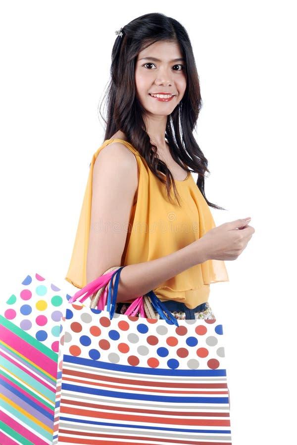 有五颜六色的购物袋的被隔绝的雍亚裔妇女 免版税库存图片
