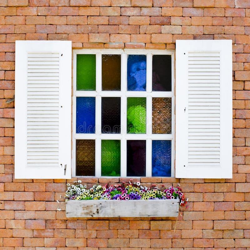 有五颜六色的玻璃的砖墙在白色窗口和美好的f里 库存图片