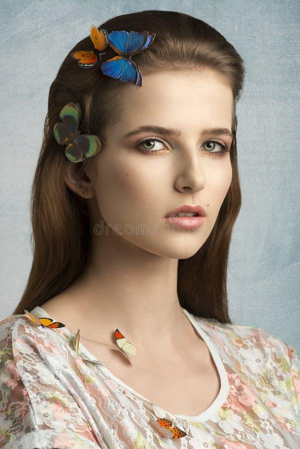 有五颜六色的蝴蝶的迷人的女孩 库存图片