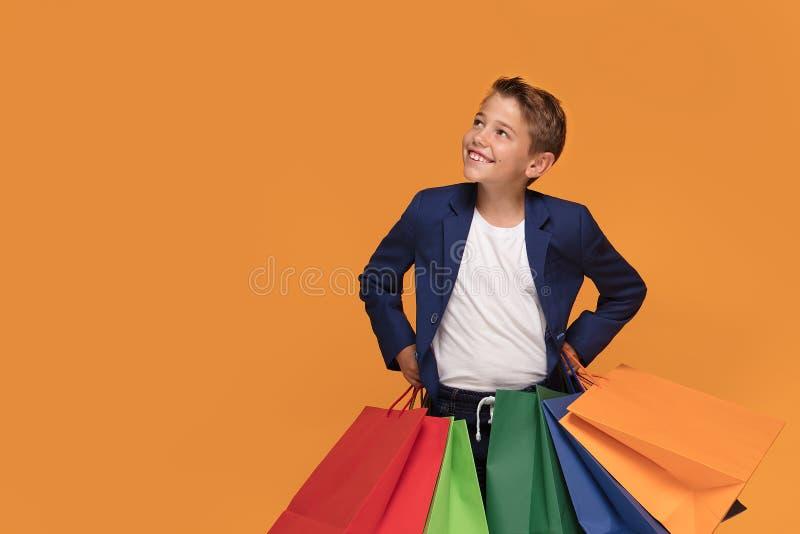 有五颜六色购物袋微笑的小男孩 免版税库存照片