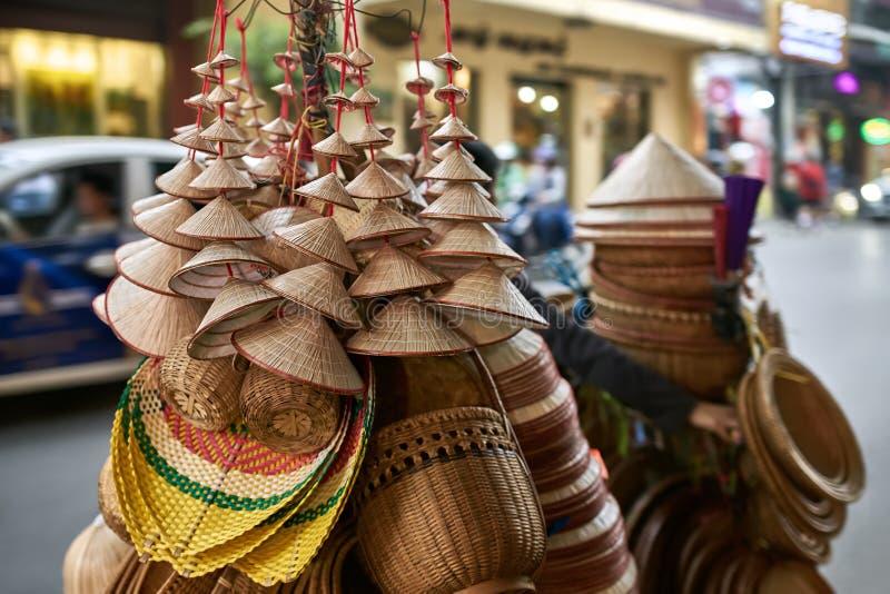 有亚洲圆锥形木帽子和篮子的街边小贩 库存照片