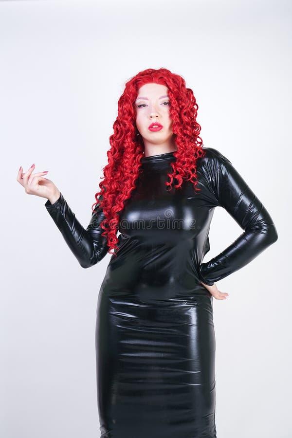 有亚洲面孔、明亮的摆在在白色backg的发光的闭合的长的黑礼服的构成和红色卷发的豪华正大小妇女 库存图片
