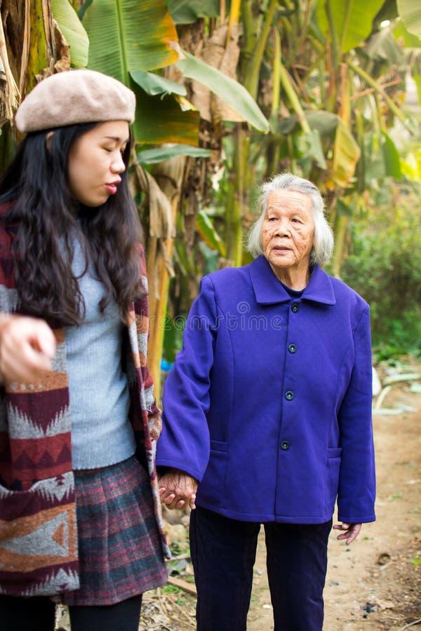 有亚裔的女孩与她的祖母的步行 免版税库存照片