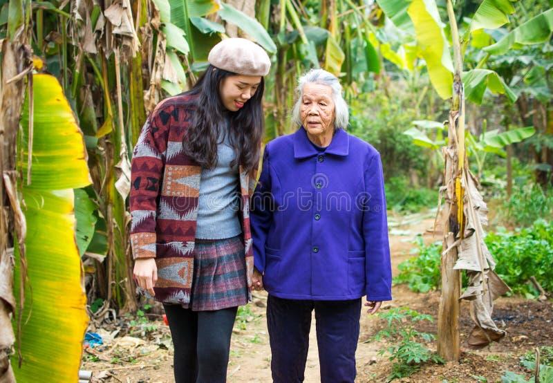有亚裔的女孩与她的祖母的步行 免版税库存图片
