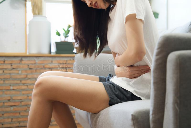 有亚裔的女孩期间坐沙发并且感觉痛苦在叫妇女的痛苦或月经的她的胃 免版税库存照片