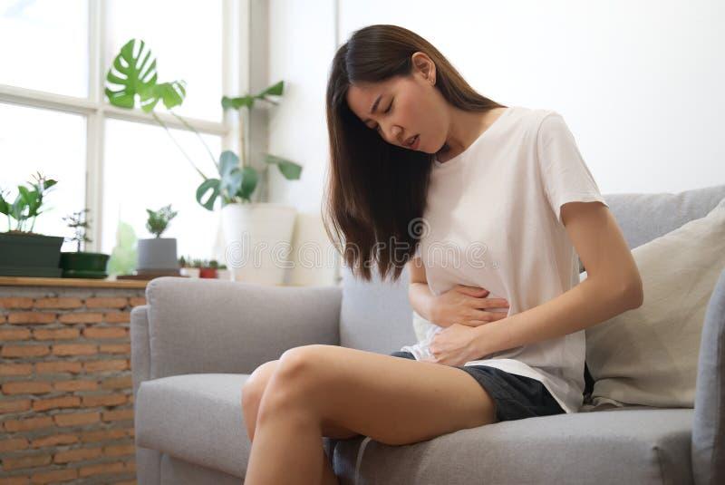 有亚裔的女孩期间坐沙发并且感觉痛苦在她的有未知的原因的胃 她保持她 免版税图库摄影