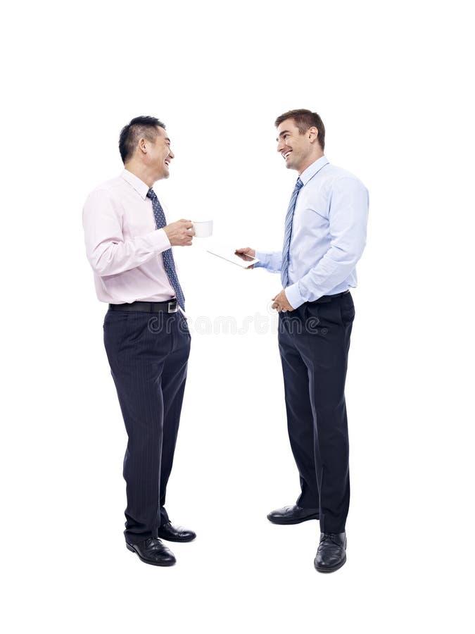有亚洲和白种人的商人交谈 免版税库存图片