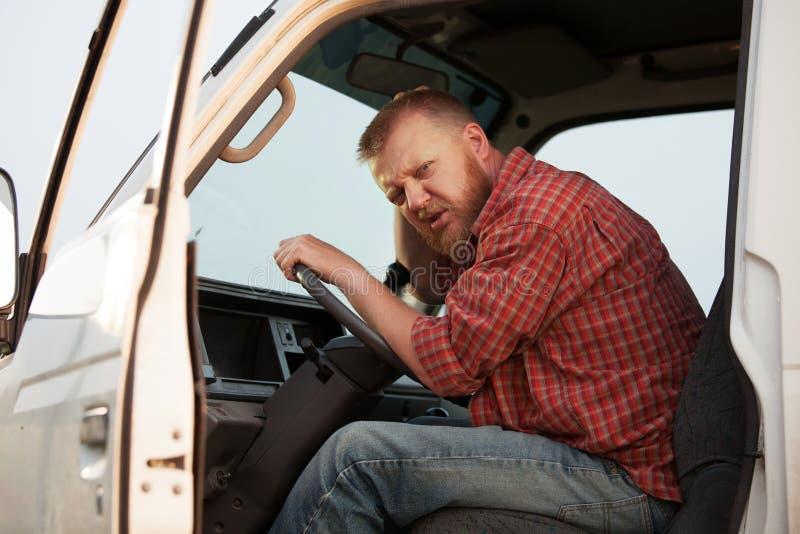 有些小室的困惑的有胡子的司机 免版税图库摄影