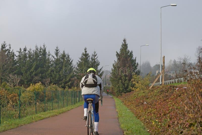 有些骑自行车者乘坐公园周期道路 免版税库存照片