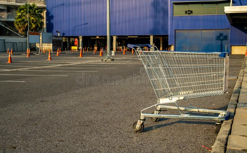 有交通锥体的手推车在商店停车场,蓝色背景 库存图片