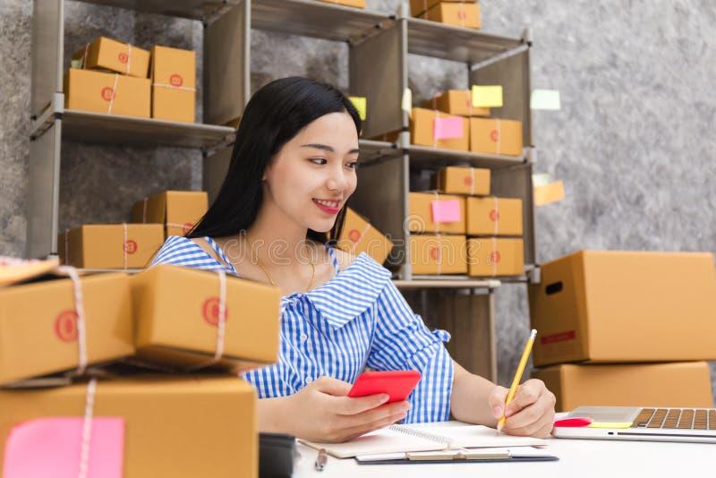 有产品包装的箱子的亚裔妇女 免版税库存照片