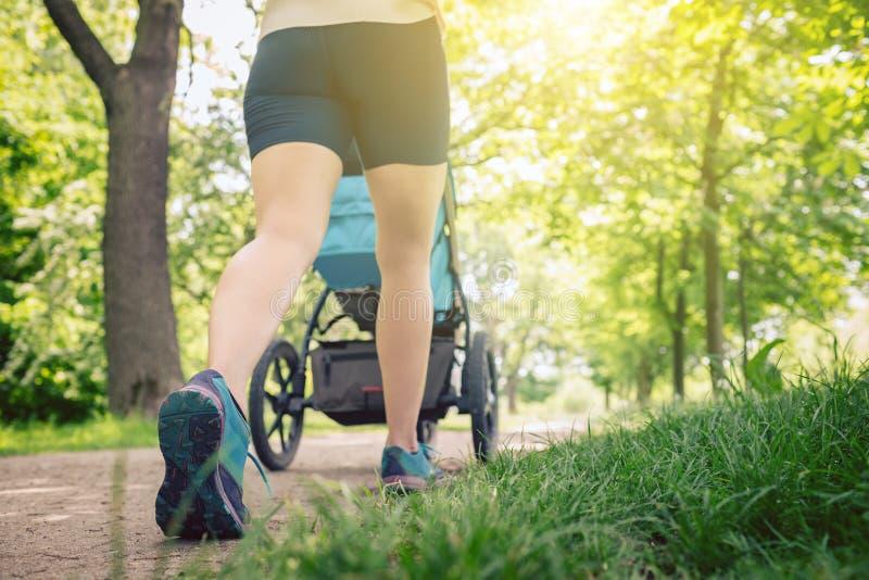 有享受夏天的婴儿车的走的妇女在公园 免版税库存图片
