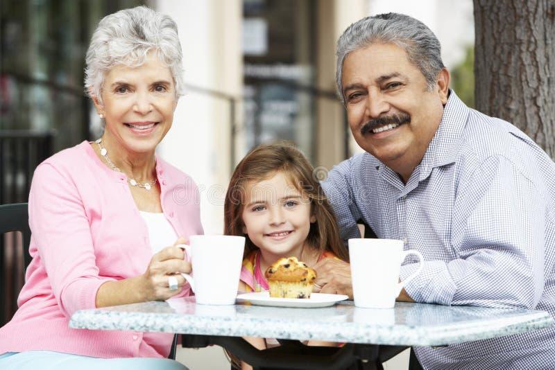 有享用快餐的孙女的祖父母在室外CafÅ ½ 库存照片
