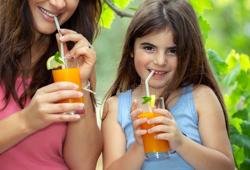 有享用汁液的女儿的母亲 免版税库存照片