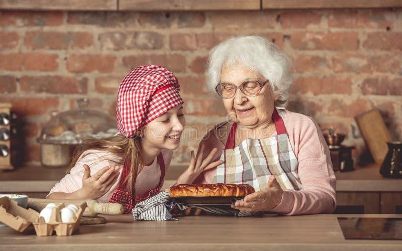 有享用自创果子饼的老婆婆的小孙女 库存图片