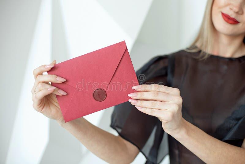 有亭亭玉立的身体的特写镜头妇女在手上的拿着邀请信封卡片,后方veaw 库存照片