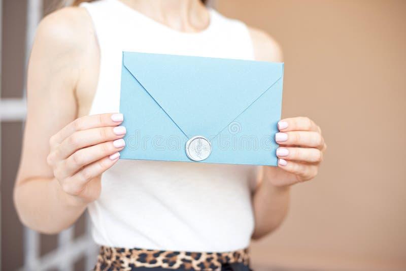 有亭亭玉立的身体藏品邀请信封卡片的在手上,后方veaw特写镜头妇女 库存照片