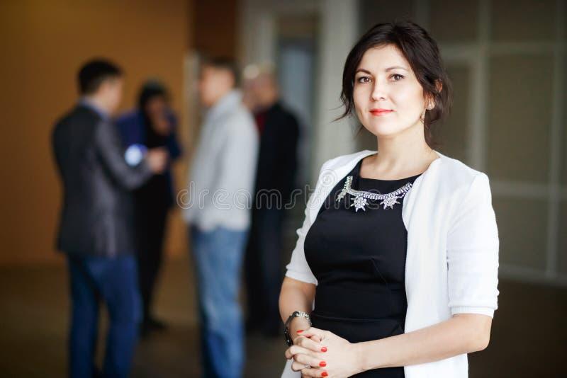 有亲切的眼睛的成功的可爱的女商人上司浅黑肤色的男人站立里面办公楼和欢迎微笑 免版税库存图片