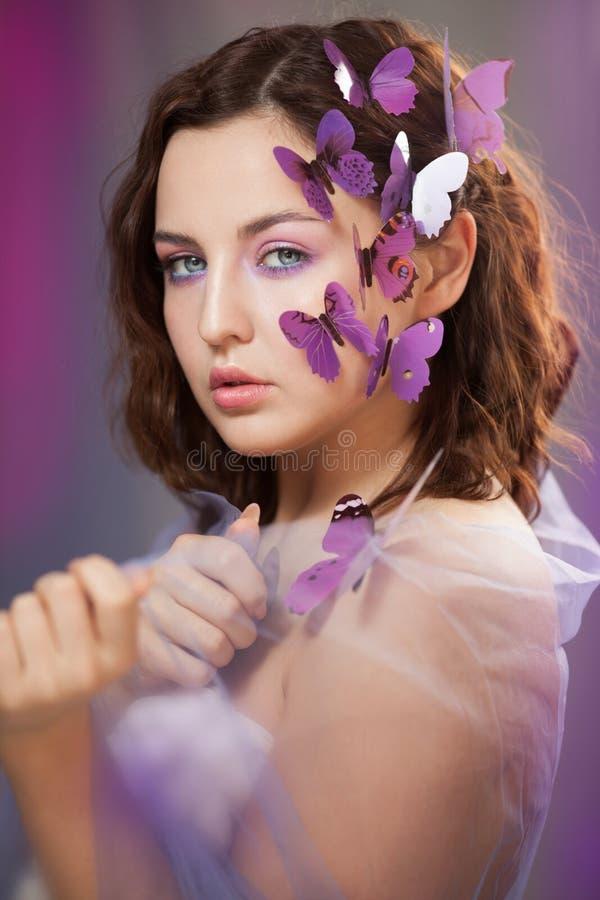 有人为蝴蝶的美丽的年轻女人在卷发 免版税图库摄影