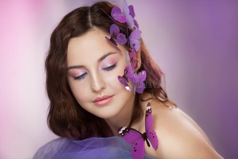 有人为蝴蝶的美丽的年轻女人在卷发 库存图片
