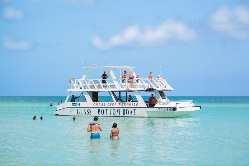 有人的惊人的美丽的平静的绿松石海洋背景游泳和走的往玻璃小船 免版税库存图片