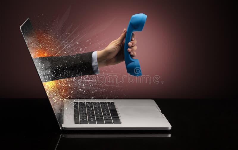 有从膝上型计算机出来的电话的手 免版税库存照片
