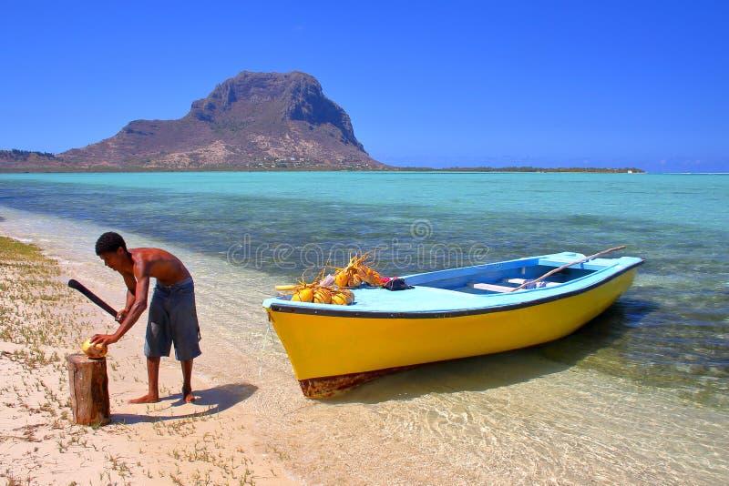 有他五颜六色的小船的一位椰子卖主在有Morne的布拉本特Benitiers海岛上在背景中 图库摄影