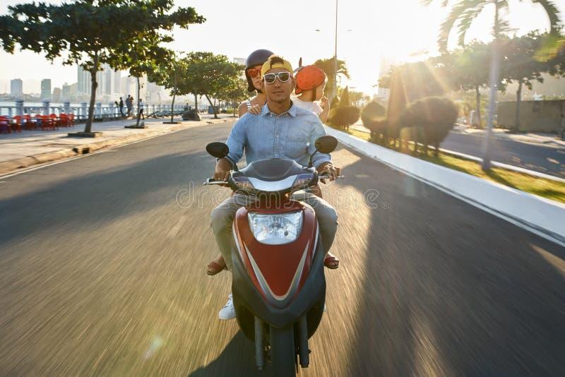 有他们的小孩骑马摩托车的父母在晴朗的城市街道上 免版税库存照片
