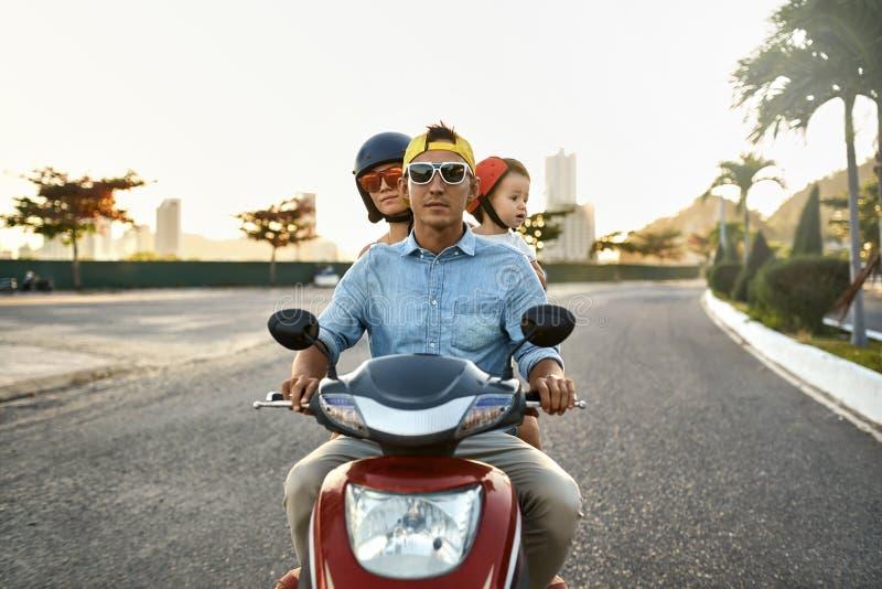 有他们的小孩骑马摩托车的父母在晴朗的城市街道上 免版税库存图片