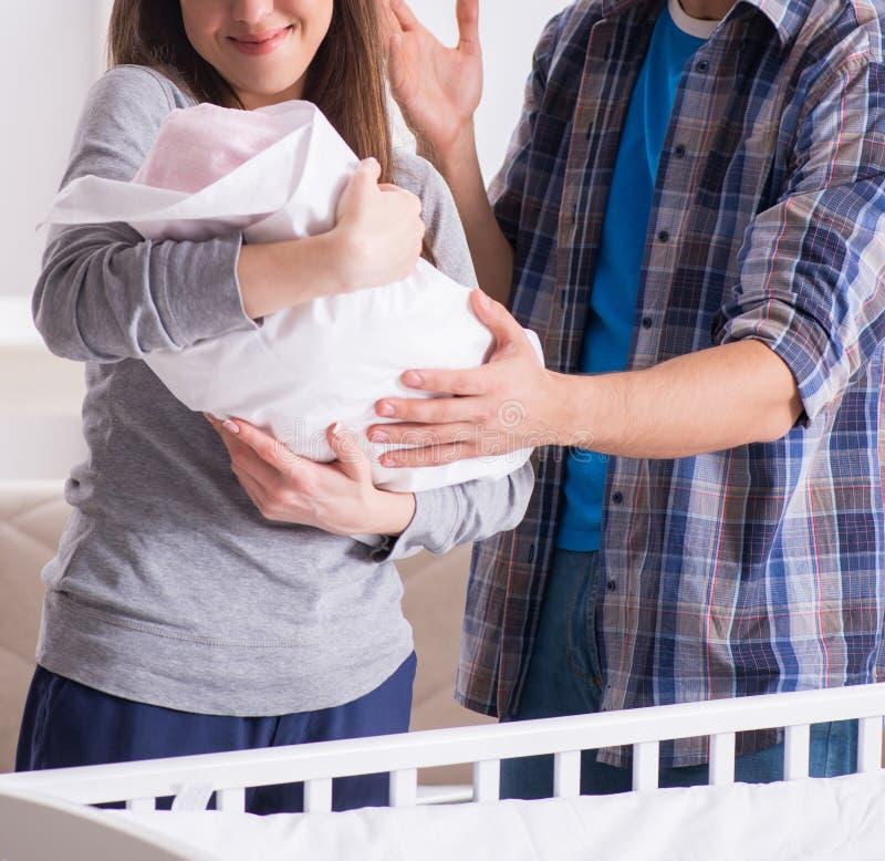 有他们的新生儿的年轻父母在床轻便小床附近 图库摄影