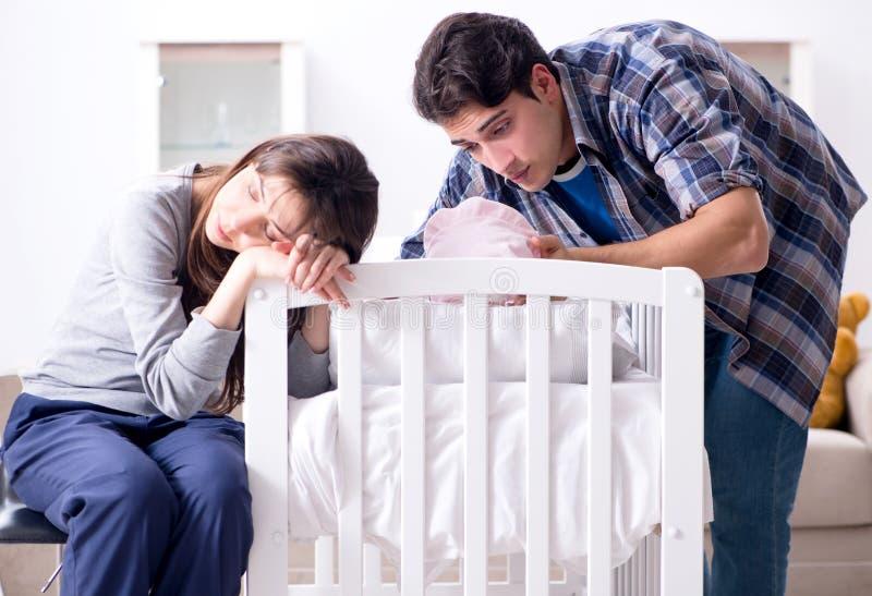 有他们的新生儿的年轻父母在床轻便小床附近 免版税库存图片