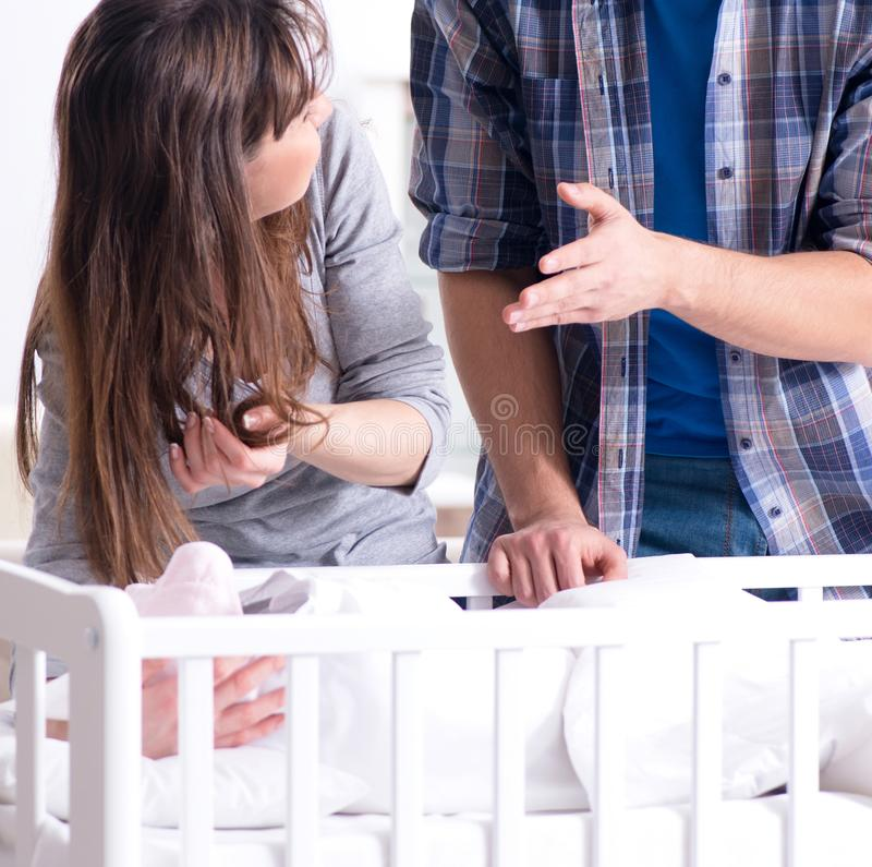 有他们的新生儿的年轻父母在床轻便小床附近 免版税库存照片
