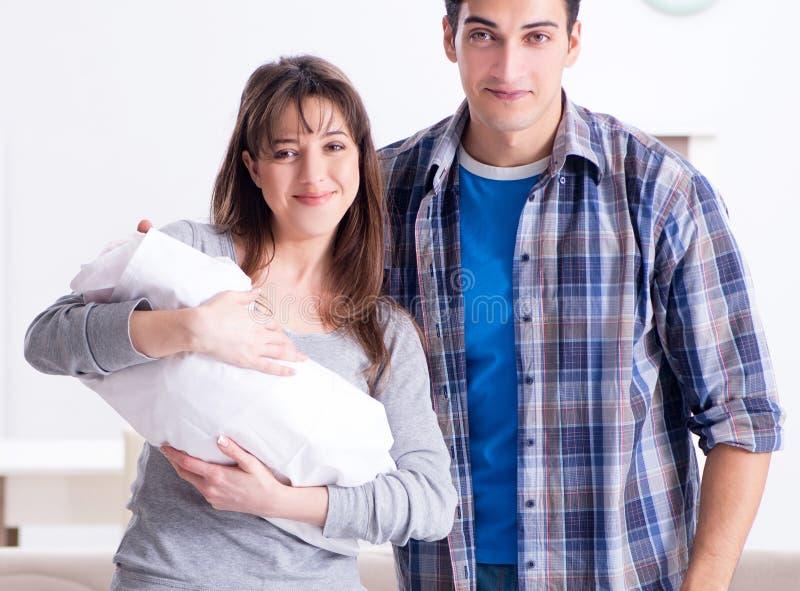 有他们的新生儿的年轻父母在床轻便小床附近 库存图片