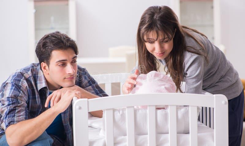 有他们的新生儿的年轻父母在床轻便小床附近 库存照片