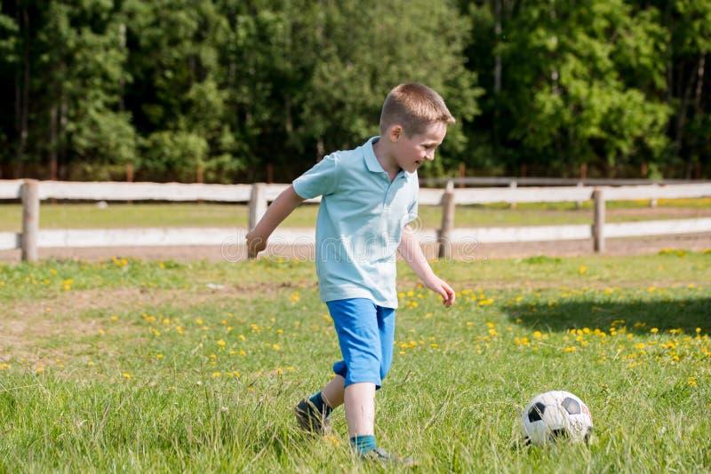 有他小的逗人喜爱的太阳的英俊的爸爸获得乐趣并且踢在绿色象草的草坪的橄榄球 库存照片