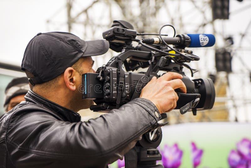 有他摄象机射击的摄影师室外在城市 免版税库存图片