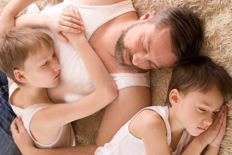 有他的二个儿子休眠的父亲 库存照片