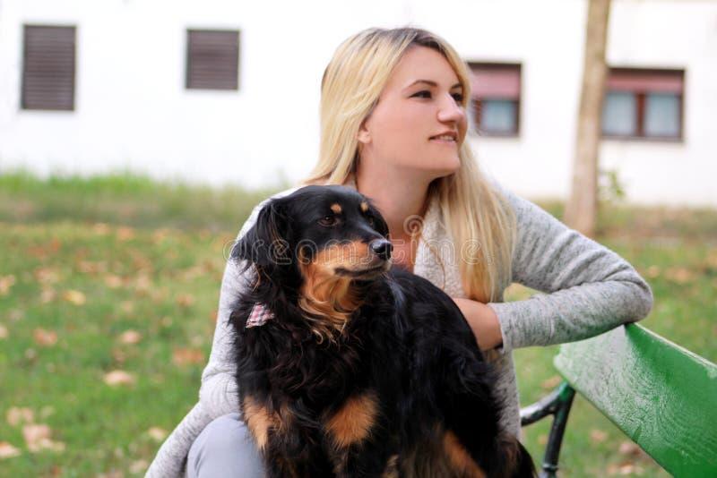 有他的坐和摆在照相机前面的小混杂的品种狗的美女在长木凳在城市公园 免版税库存照片
