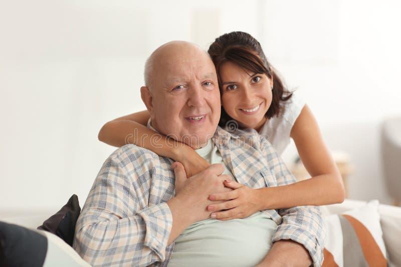有他的女儿的愉快的年长人在家 图库摄影