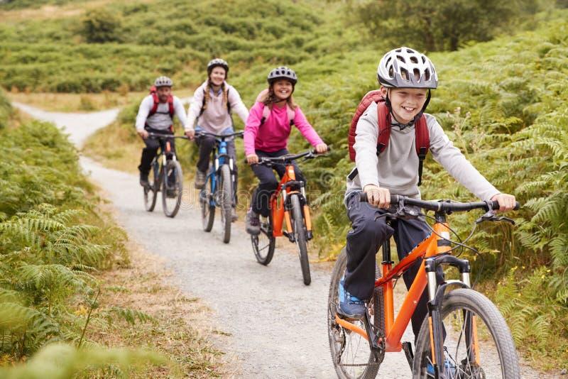 有他的姐妹和父母的在家庭野营期间,关闭青春期前的男孩骑马登山车 免版税库存图片