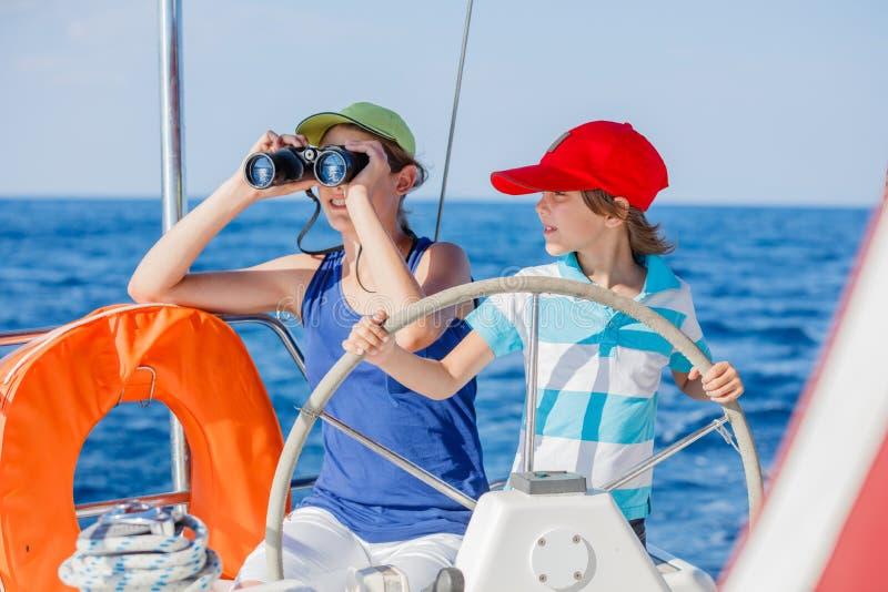 有他的姐妹的男孩上尉在船上在夏天巡航的航行游艇 旅行冒险,乘快艇与家庭的孩子 免版税库存照片