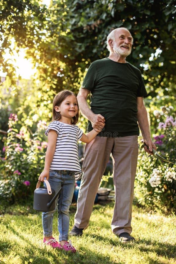 有他的孙女的老人在晴朗的后院 免版税库存图片