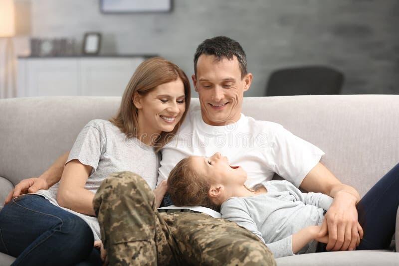 有他的家庭的军事父亲在沙发 免版税库存照片