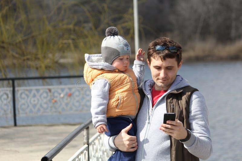 有他的小儿子的愉快的父亲他的胳膊的户外 免版税库存图片